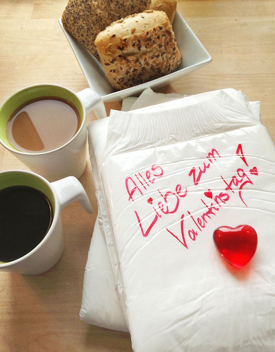 """Windel, beschriftet mit """"Alles Liebe zum Valentinstag!"""", liegt auf Frühstückstisch"""