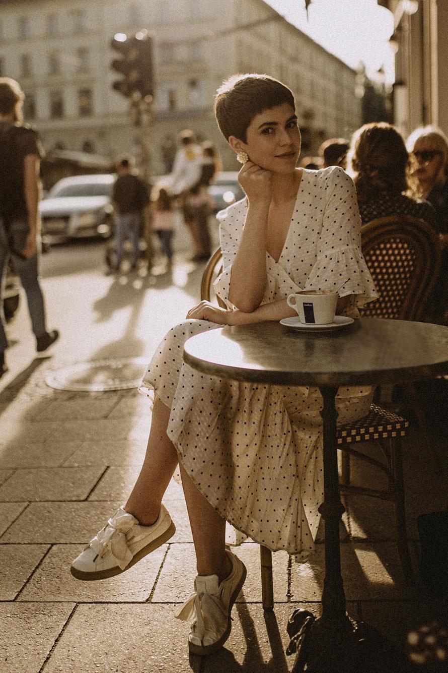 Junge Frau in hellem Sommerkleid sitzt in einem Straßencafé