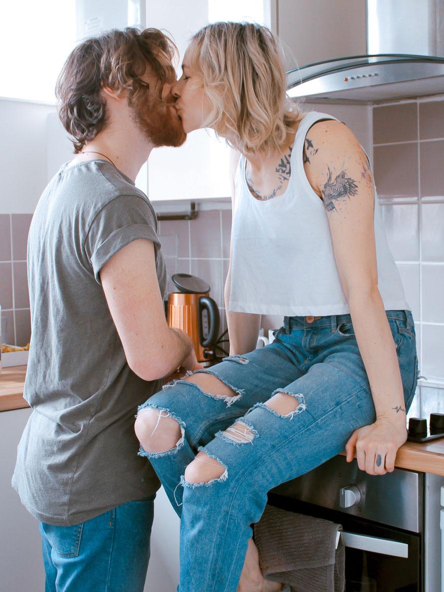 Symbolbild: Junges Paar küsst sich in der Küche.