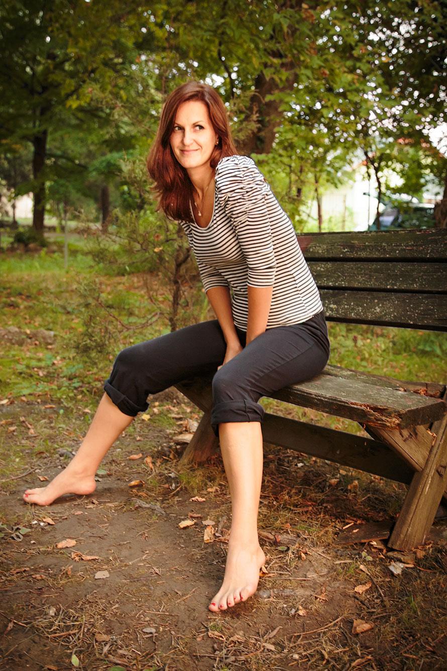 Schelmisch blickende Frau auf Bank, bevor sie sich absichtlich in die Hose pinkelt