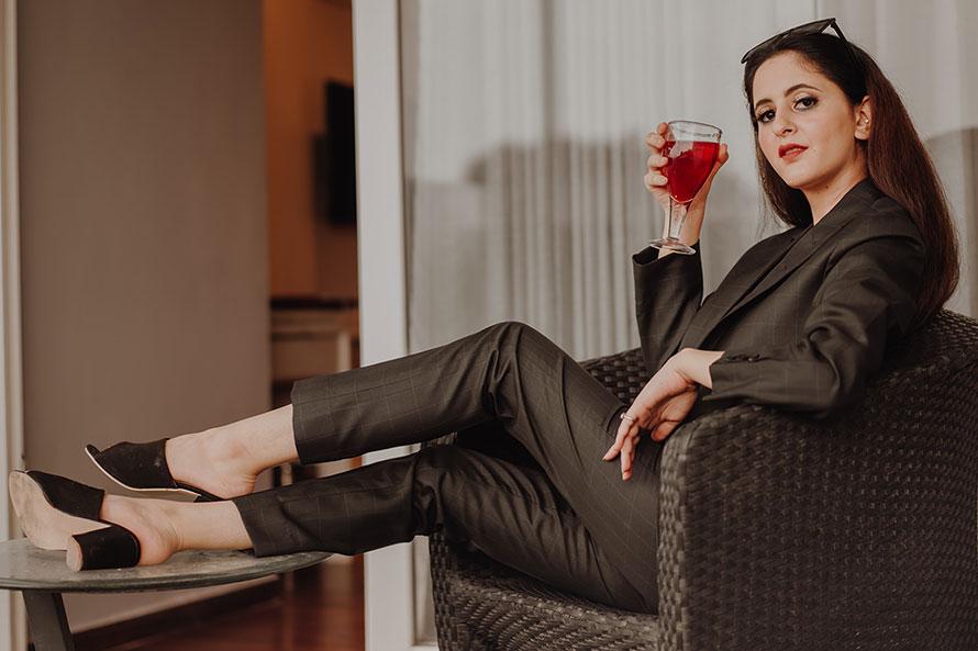 Brünette Frau mit Cocktailglas in Rattansessel