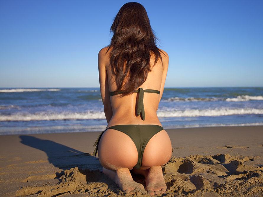 Symbolbild zur Urlaub und Reisen: Frau mit Bikini kniet am Meer im Sand.