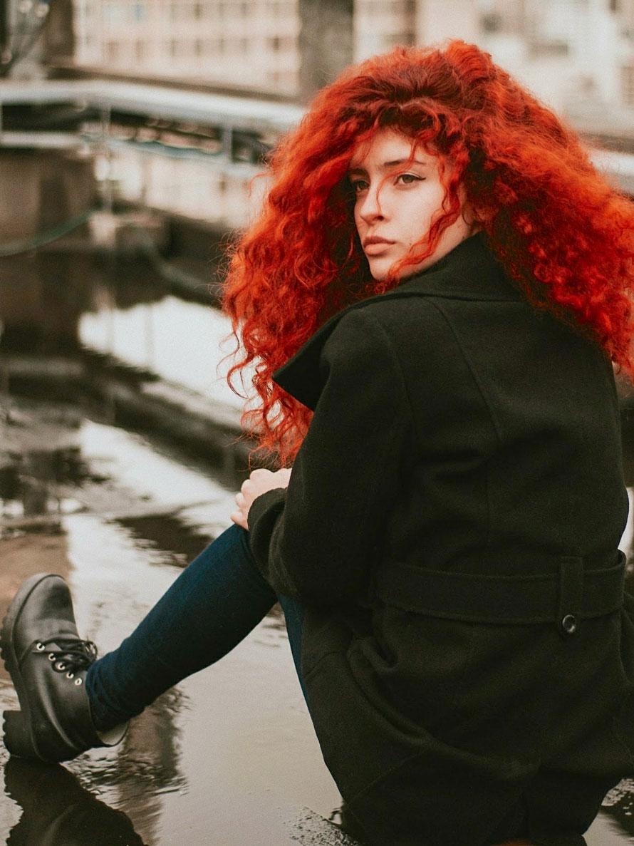 Symbolbild: Rothaariges Female-Model sitzt auf einem Hochhausdach in einer Regenpfütze.