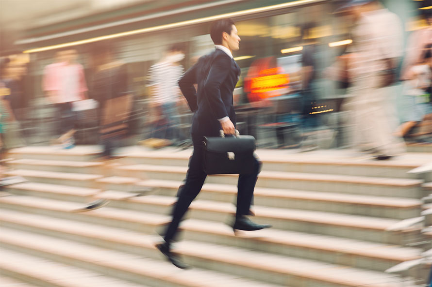 Junger Mann im Anzug mit Aktentasche rennt durch die Innenstadt.