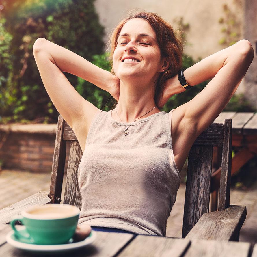 Rothaarige Frau lehnt sich genießerisch auf einem Gartenstuhl zurück