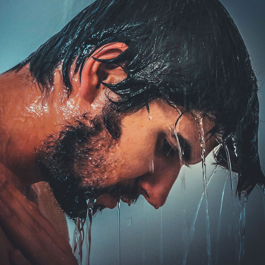 Dunkelhaariger Mann unter der Dusche.