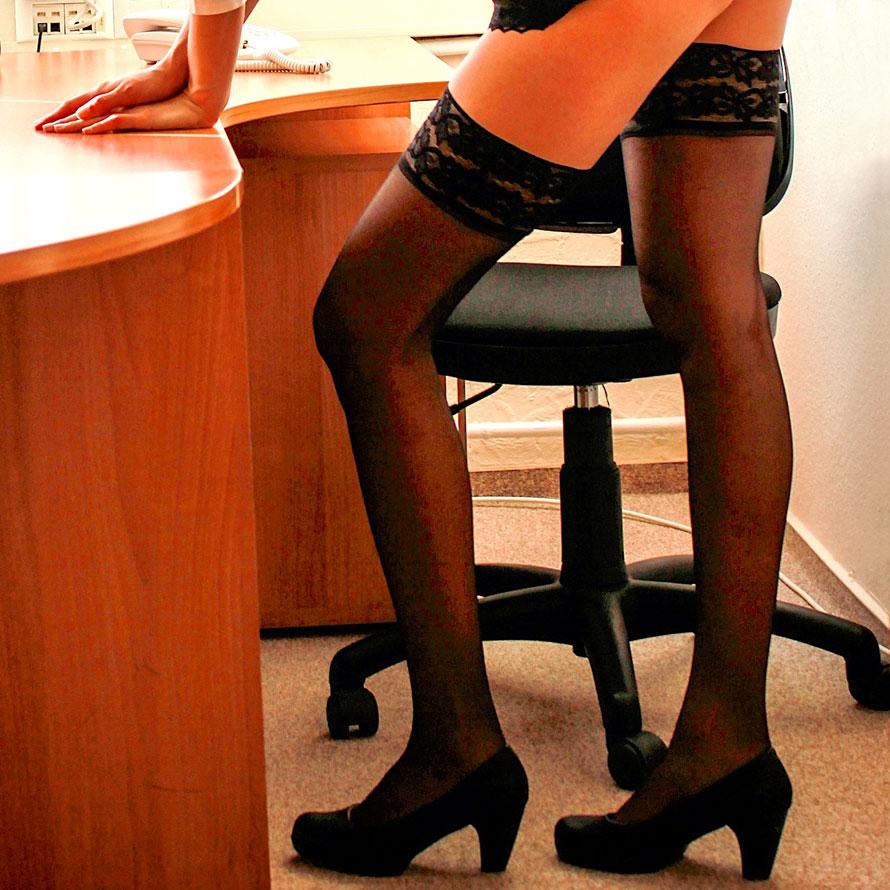 Sekretärin in kurzem Rock und halterlosen, schwarzen Nylonstrümpfen steht lasziv an einem Schreibtisch.