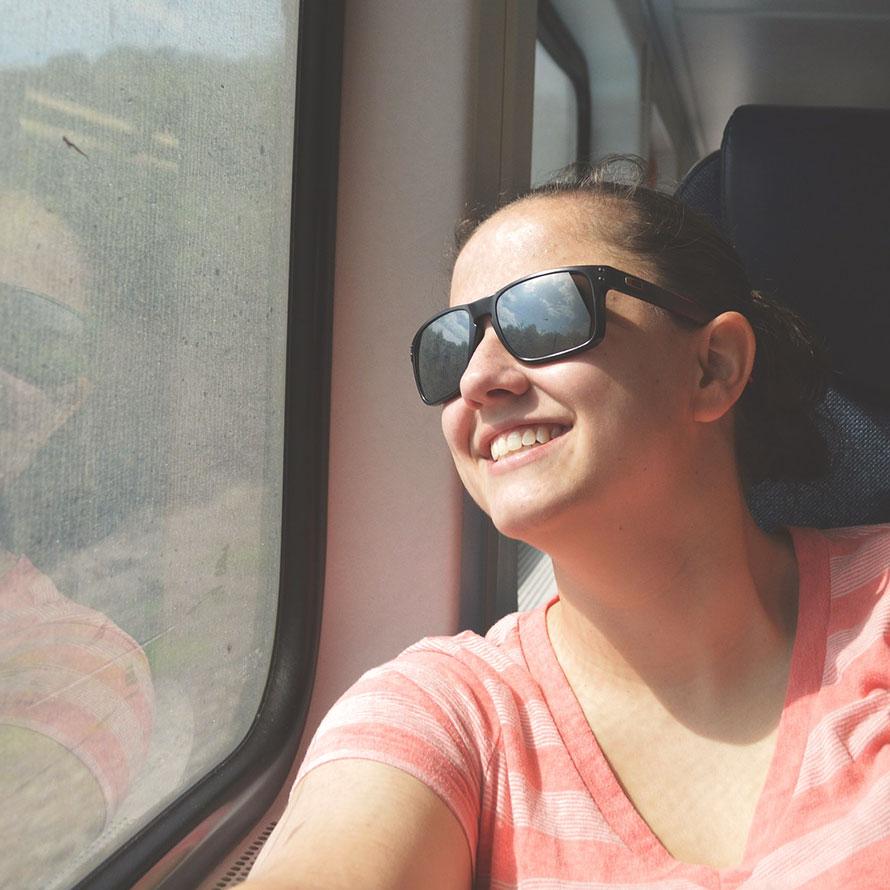 Junge Frau mit Sonnenbrille sitzt entspannt im Zug