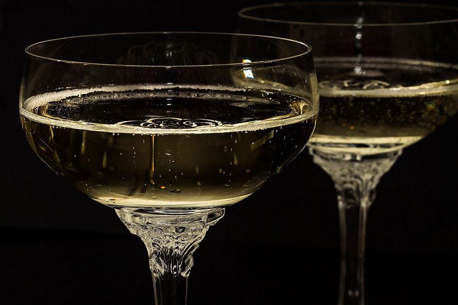 2 Champagnerschalen aus Kristallglas, halb gefüllt