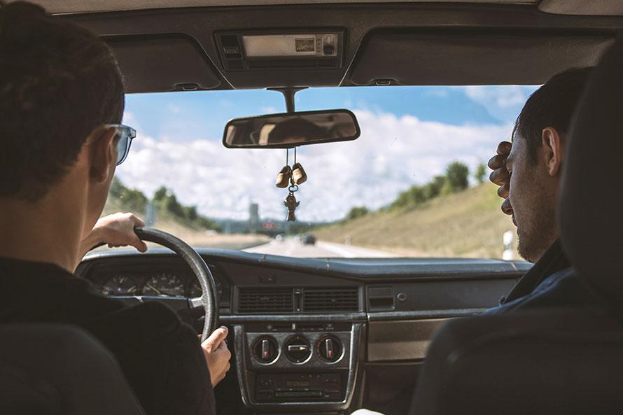 Zwei junge Männer unterwegs im Auto auf der Autobahn