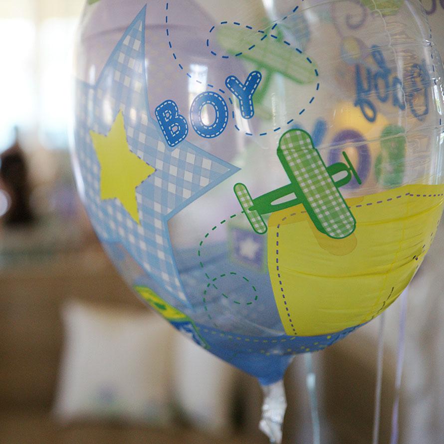 """Durchsichtiger Luftballon mit der Aufschrift """"Boy"""" und aufgedrucktem Flugzeugmotiv"""" in gemütlich dekoriertem Zimmer"""